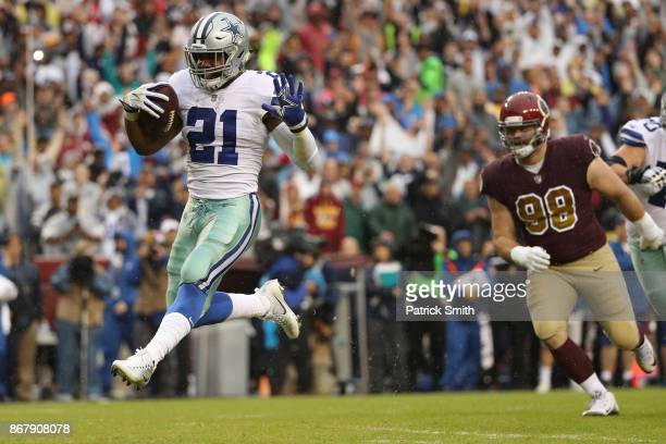 Running back Ezekiel Elliott of the Dallas Cowboys runs for a touchdown against the Washington Redskins during the first quarter at FedEx Field on...