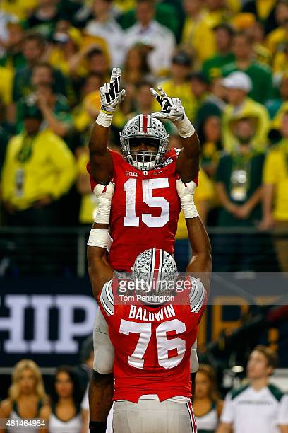 Running back Ezekiel Elliott of the Ohio State Buckeyes celebrates with offensive lineman Darryl Baldwin after Elliott scored a 9yard touchdown in...