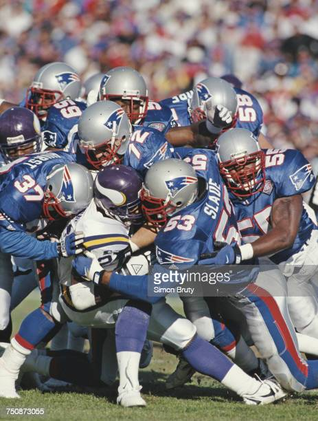Running back for the Minnesota Vikings Terry Allen is tackled by Chris Slade #37 Maurice Hurst #55 Willie McGinst and Tim Goad of the New England...