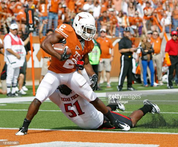 Running back Fozzy Whittaker of the Texas Longhorns scores a second quarter touchdown against linebacker Cqulin Hubert of the Texas Tech Red Raiders...