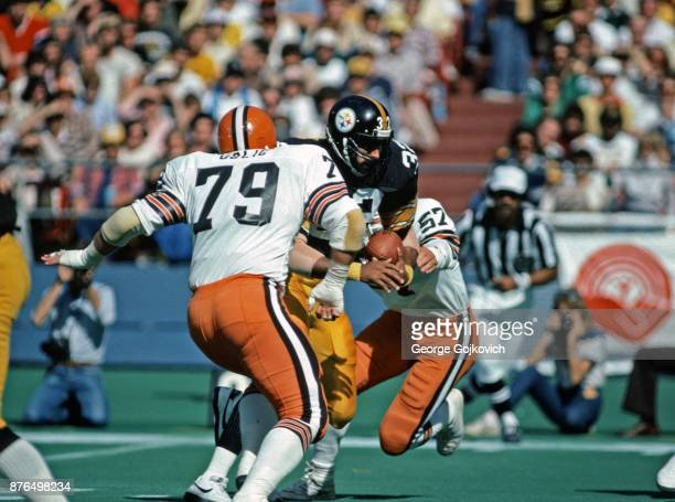 Running back Franco Harris of the Pittsburgh Steelers runs with the football as he is pursued by defensive lineman Bob Golic and linebacker Clay...