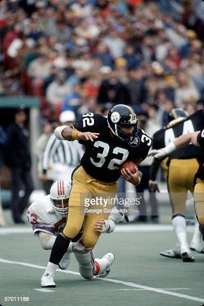 Running back Franco Harris of the Pittsburgh Steelers tries to elude the tackle of linebacker Clayton Weishuhn of the New England Pariots at Three...