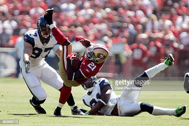 Running back Frank Gore of the San Francisco 49ers breaks a tackle by cornerback Ken Lucas and defensive end Patrick Kerney of the Seattle Seahawks...