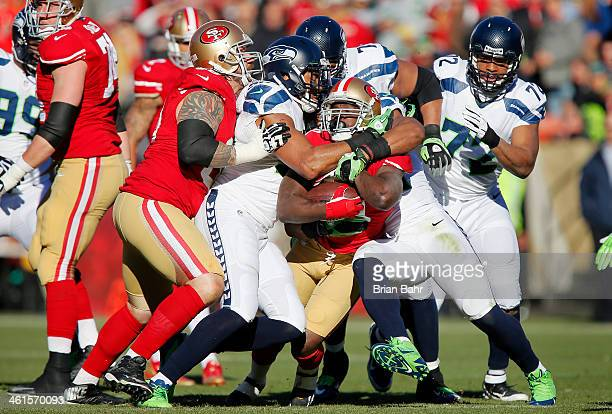 Running back Frank Gore of the San Francisco 49ers gets ganged up on by linebacker KJ Wright and free safety Earl Thomas of the Seattle Seahawks in...