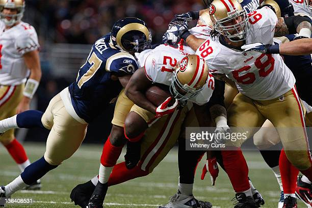 Running back Frank Gore of the San Francisco 49ers runs the ball ahead of teammate Adam Snyder and free safety Quintin Mikell of the St Louis Rams on...