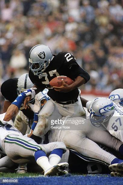 Running back Frank Hawkins of the Los Angeles Raiders battles for extra yards against the Seattle Seahawks defense during the 1983 AFC Conference...