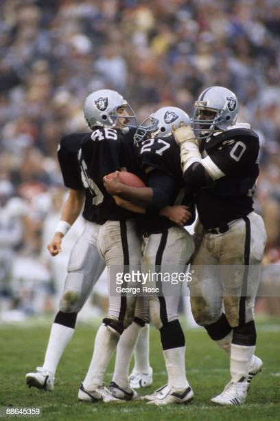 Running back Frank Hawkins of the Los Angeles Raiders celebrates with teammates Tight end Todd Christensen and offensive lineman Henry Lawrence...
