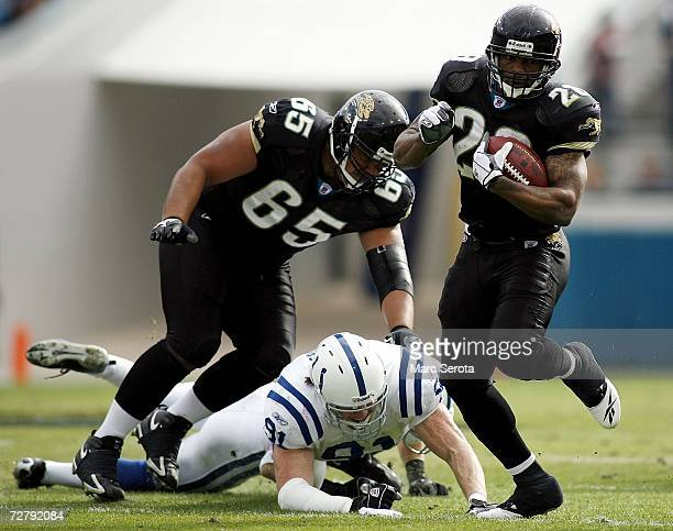 Running Back Fred Taylor of the Jacksonville Jaguars runs the ball against defensive lineman Josh Thomas of the Indianapolis Colts as offensive...
