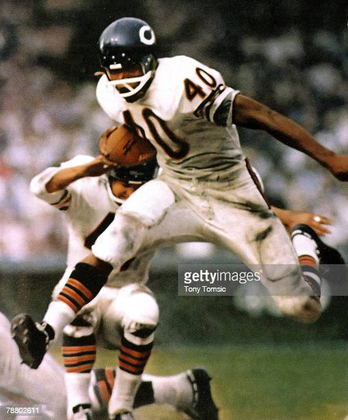 Running back Gayle Sayers of the Chicago Bears leaps a defender while heading upfield with the ball