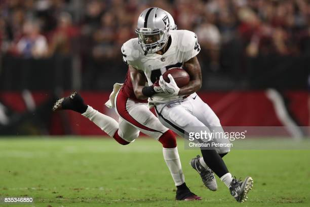 Running back George Atkinson of the Oakland Raiders runs with the football after a reception past free safety Harlan Miller of the Arizona Cardinals...