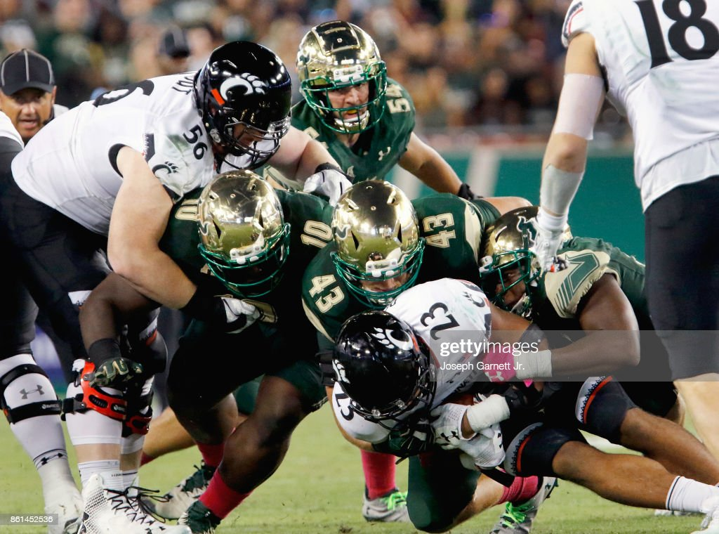 Running back Gerrid Doaks #23 of the Cincinnati Bearcats is brought down by the defense led by linebacker Auggie Sanchez #43 of the South Florida Bulls during the third quarter of their game at Raymond James Stadium on October 14, 2017 in Tampa, Florida.