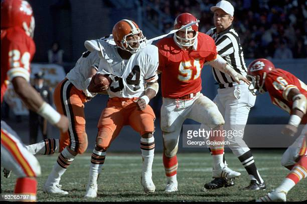 Running back Greg Pruitt of the Cleveland Browns has his jersey torn by linebacker Jim Lynch of the Kansas City Chiefs at Municipal Stadium on...