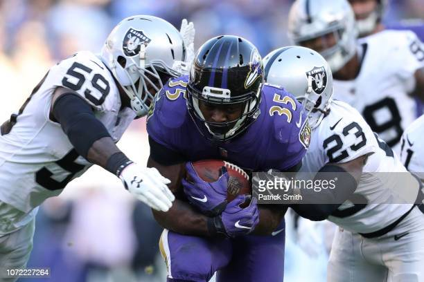 Running Back Gus Edwards of the Baltimore Ravens is tackled as he carries the ball by cornerback Nick Nelson and outside linebacker Tahir Whitehead...