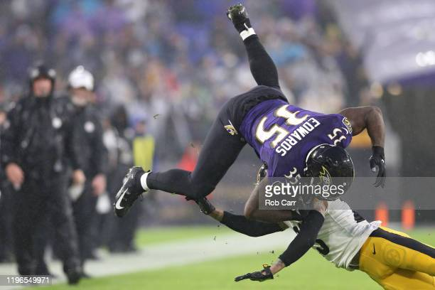 Running back Gus Edwards of the Baltimore Ravens is tackled by cornerback Joe Haden of the Pittsburgh Steelers during the first quarter at MT Bank...