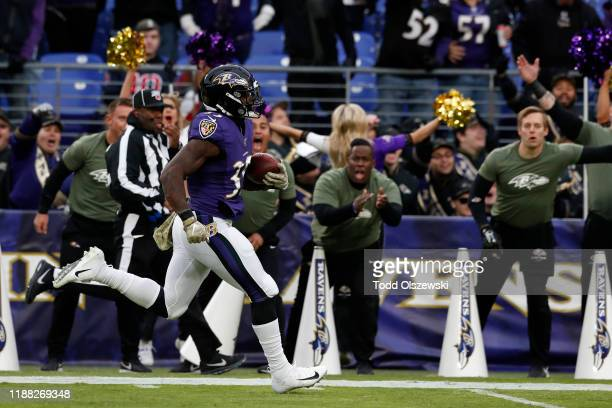 Running Back Gus Edwards of the Baltimore Ravens runs for a touchdown during the second half against the Houston Texans at MT Bank Stadium on...