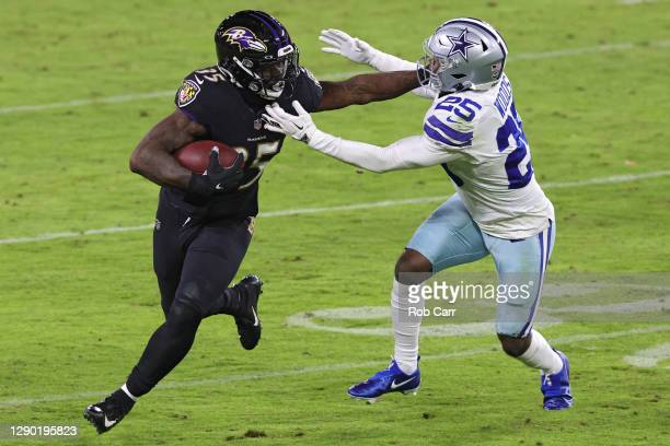 Running back Gus Edwards of the Baltimore Ravens rushes past free safety Xavier Woods of the Dallas Cowboys during the fourth quarter at M&T Bank...