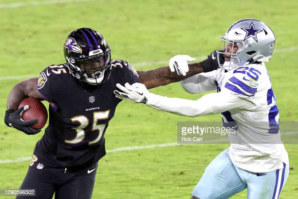 Running back Gus Edwards of the Baltimore Ravens stiff arms free safety Xavier Woods of the Dallas Cowboys at M&T Bank Stadium on December 03, 2020...
