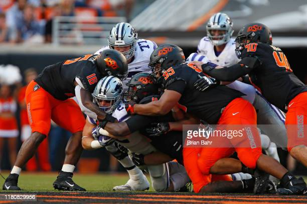 Running back Harry Trotter of the Kansas State Wildcats gets swarmed for no gain by linebacker Devin Harper linebacker Amen Ogbongbemiga and...