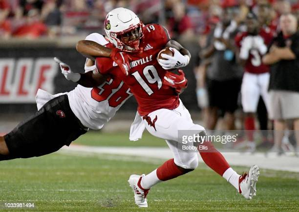 Running back Hassan Hall of the Louisville Cardinals shrugs off defensive back Kyle Bailey of the Western Kentucky Hilltoppers as he runs down the...