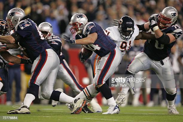 Running back Heath Evans of the New England Patriots runs with a block from guard Logan Mankins against defensive tackle Tommie Harris of the Chicago...