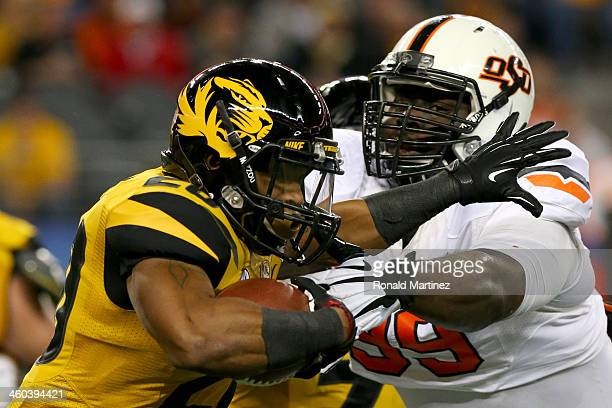 Running back Henry Josey of the Missouri Tigers runs against Calvin Barnett of the Oklahoma State Cowboys in the first half during the AT&T Cotton...