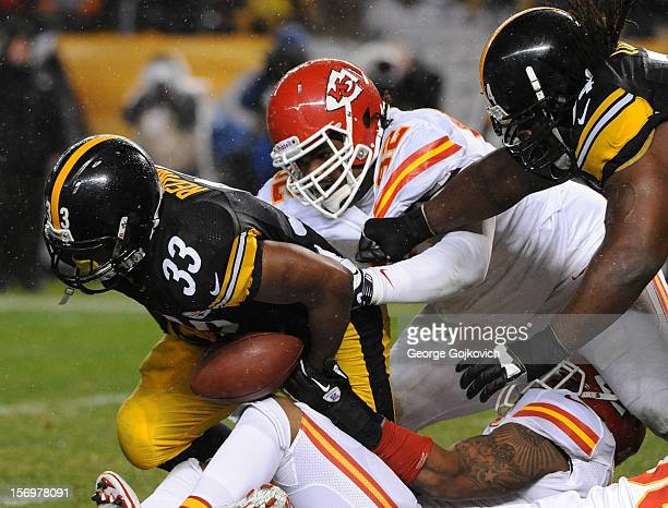 Running back Isaac Redman of the Pittsburgh Steelers fumbles the football as his arm is grabbed by linebacker Derrick Johnson and he is hit by...