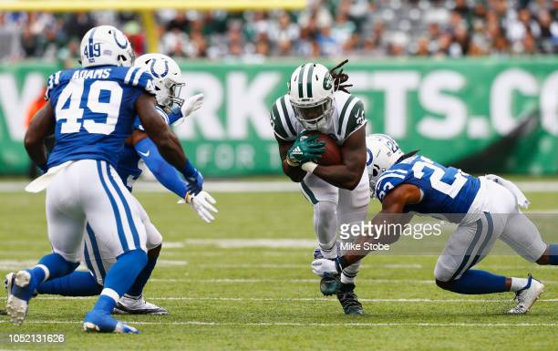 Running back Isaiah Crowell of the New York Jets runs the ball against cornerback Kenny Moore and linebacker Anthony Walker of the Indianapolis Colts...