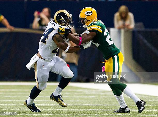 Running back Isaiah Pead of the St Louis Rams his held back by cornerback Jarrett Bush of the Green Bay Packers during the game at the Edward Jones...