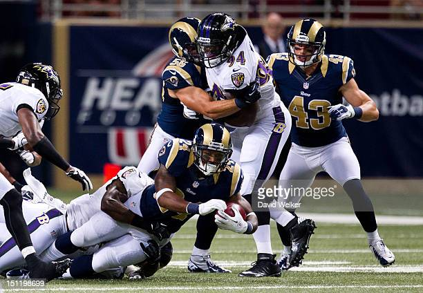Running back Isaiah Pead of the St Louis Rams is tackled on a play during the game against the Baltimore Ravens at the Edward Jones Dome on August 30...