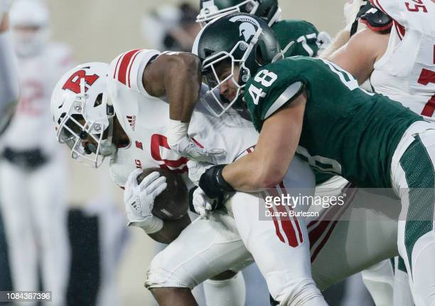 Running back Isaih Pacheco of the Rutgers Scarlet Knights is tackled by defensive end Kenny Willekes of the Michigan State Spartans during the first...