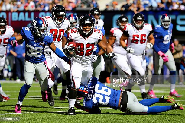 Running back Jacquizz Rodgers of the Atlanta Falcons runs the ball against Cornerback Trumaine McBride and strong safety Antrel Rolle of the New York...
