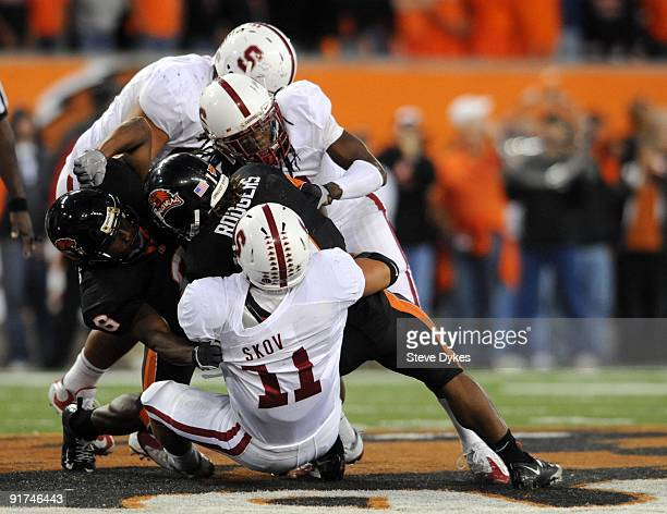 Running back Jacquizz Rodgers of the Oregon State Beavers is tackled by linebacker Shayne Skov and cornerback Richard Sherman of Stanford Cardinals...