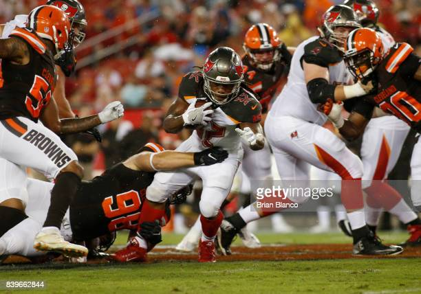 Running back Jacquizz Rodgers of the Tampa Bay Buccaneers is stopped by defensive end Jamie Meder of the Cleveland Browns during the first quarter of...