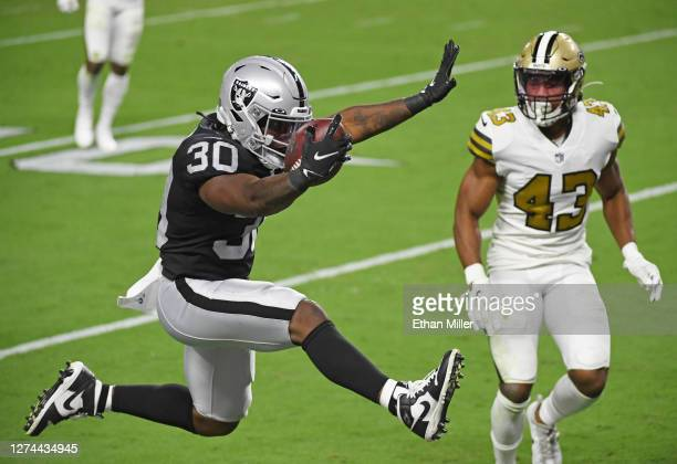 Running back Jalen Richard of the Las Vegas Raiders leaps into the end zone to score a 20-yard rushing touchdown ahead of free safety Marcus Williams...