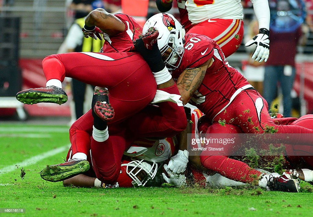 Running back Jamaal Charles #25 of the Kansas City Chiefs is tacked by middle linebacker Larry Foote #50 of the Arizona Cardinals (R) and free safety Rashad Johnson #26 (L) in the first half of the NFL game at University of Phoenix Stadium on December 7, 2014 in Glendale, Arizona.