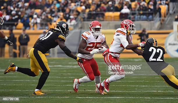 Running back Jamaal Charles of the Kansas City Chiefs runs from linebacker Sean Spence of the Pittsburgh Steelers as wide receiver Frankie Hammond Jr...