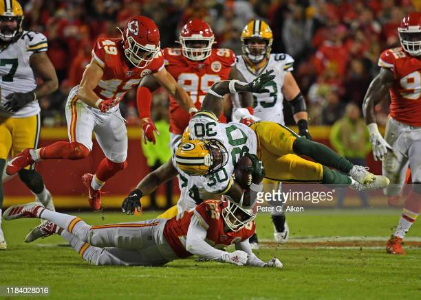 Running back Jamaal Williams of the Green Bay Packers gets tripped up by free safety Juan Thornhill of the Kansas City Chiefs during the second half...