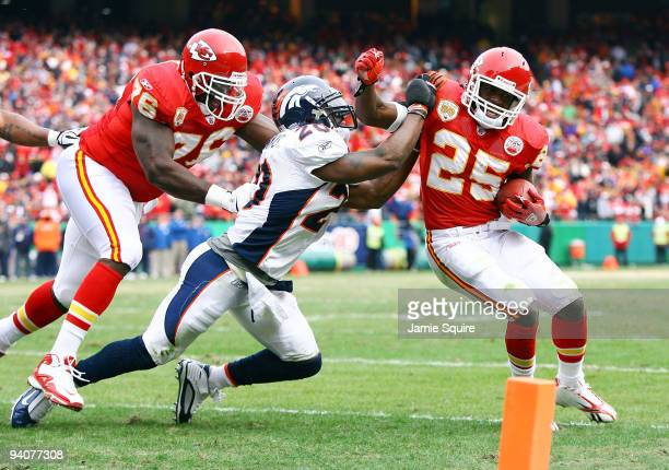 Running back Jamal Charles of the Kansas City Chiefs tries to turn the corner as safety Brian Dawkins of the Denver Broncos defends during the game...