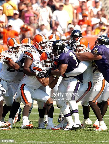 Running back Jamal Lewis of the Baltimore Ravens is gangtackled by defensive back Earl Little defensive linemen Alvin McKinley and Michael Myers and...
