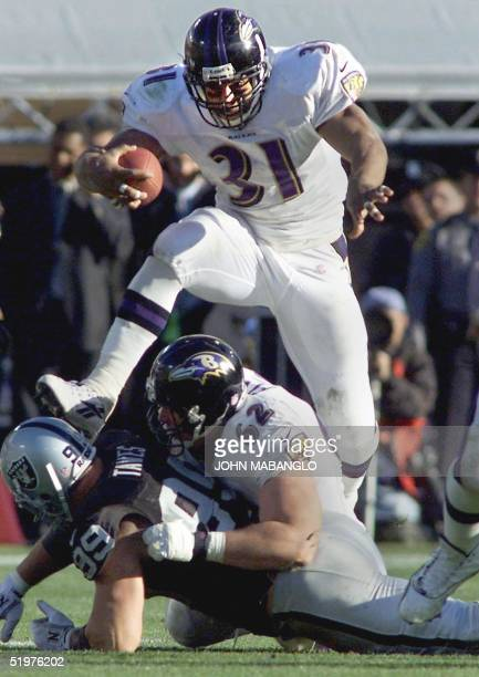 Running back Jamal Lewis of the Baltimore Ravens jumps over his blockers for a gain against the Oakland Raiders in their AFC Championship game 14...