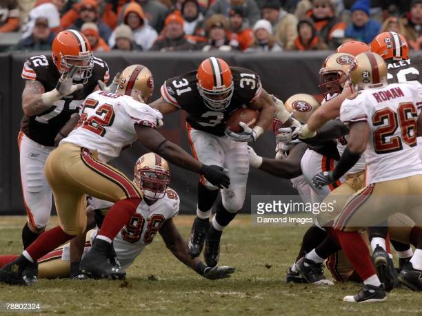 Running back Jamal Lewis of the Cleveland Browns carries the ball as linebackers Patrick Willis and Parys Haralson and defensive back Mark Roman of...