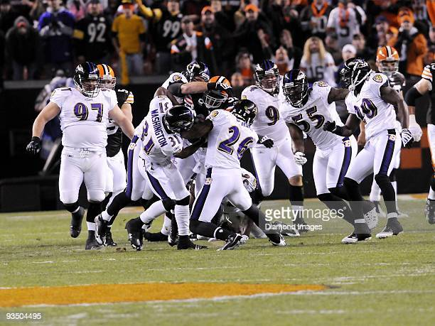 Running back Jamal Lewis of the Cleveland Browns is gangtackled by defensive backs Fabian Washington and Dawan Landry as defensive linemen Kelly...