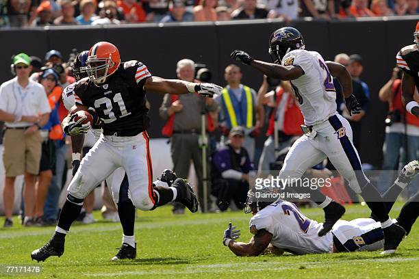 Running back Jamal Lewis of the Cleveland Browns runs away from defensive backs Chris McAlister and Ed Reed after escaping the grasp of Dawan Landry...