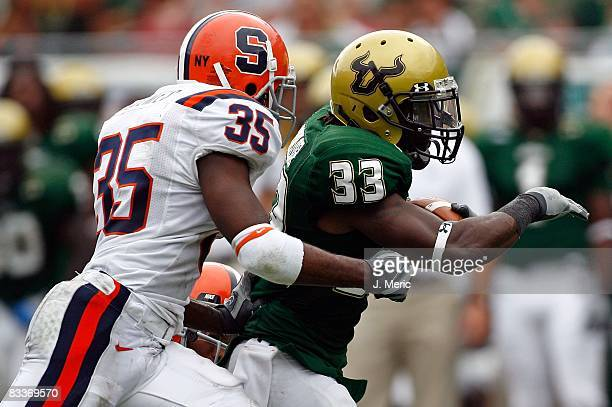 Running back Jamar Taylor of the South Florida Bulls runs from defender Mike Holmes of the Syracuse Orange during the game at Raymond James Stadium...
