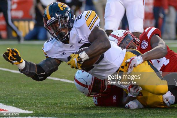 Running back James Butler of the Iowa Hawkeyes reaches across the goal line ahead of the tackle of defensive back Aaron Williams of the Nebraska...