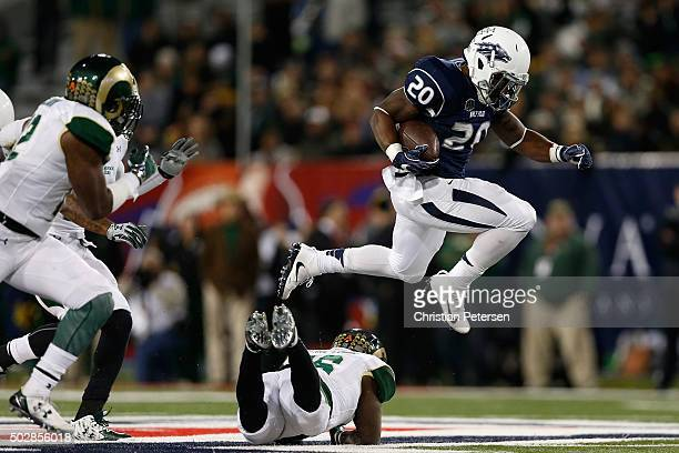 Running back James Butler of the Nevada Wolf Pack leaps over safety Trent Matthews of the Colorado State Rams as he rushes the football during the...