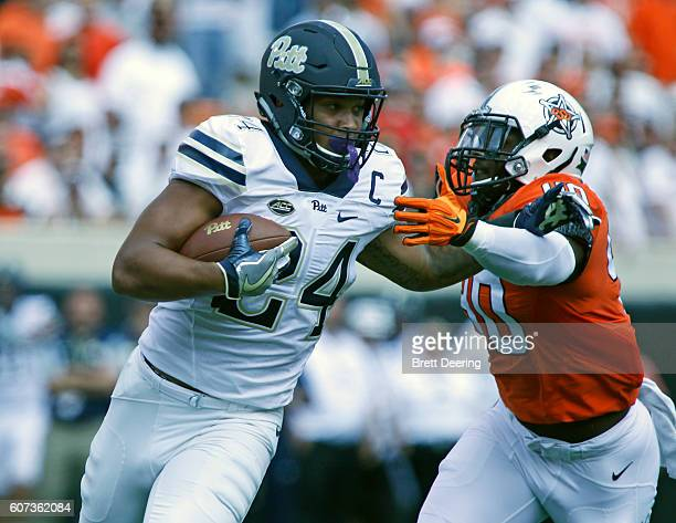 Running back James Conner of the Pittsburgh Panthers is pursued by linebacker Devante Averette of the Oklahoma State Cowboys September 17 2016 at...
