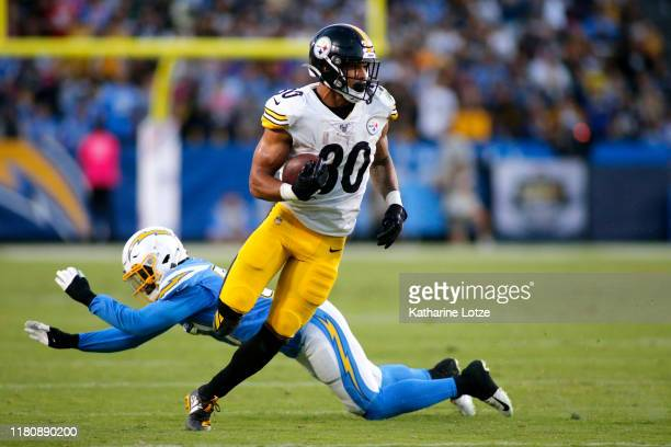 Running back James Conner of the Pittsburgh Steelers breaks through a tackle by outside linebacker Jatavis Brown of the Los Angeles Chargers for a...