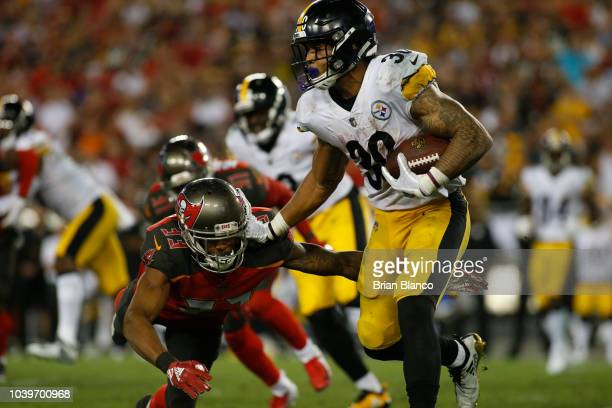 Running back James Conner of the Pittsburgh Steelers fends off cornerback Carlton Davis of the Tampa Bay Buccaneers during a carry in the third...