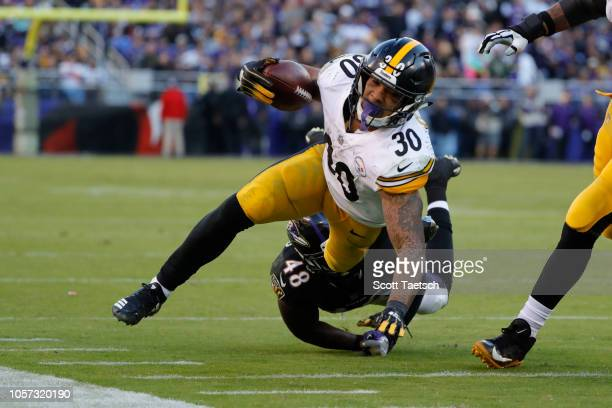 Running Back James Conner of the Pittsburgh Steelers is tackled by inside linebacker Patrick Onwuasor of the Baltimore Ravens in the fourth quarter...